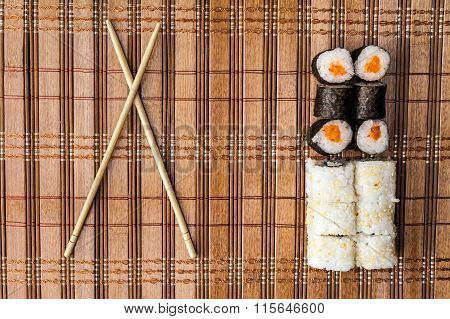 Chopsticks And Sushi Roll On Bamboo Mat. Background Menu