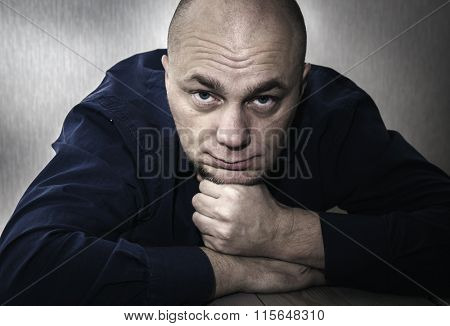 Sad man sitting at the table, leaning on his hands