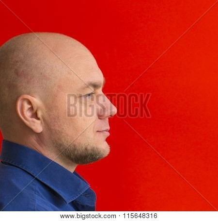Portrait of a bald man with a red background - view profile.