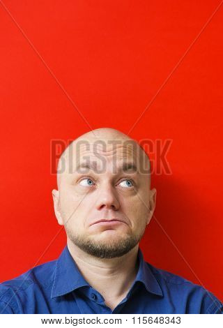 Bald adult man looking up. Red background.