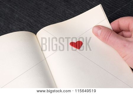 Love story. Red decorative heart on a book page. Concept of Valentines Day