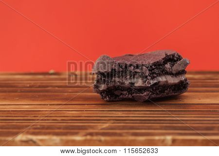 Purple Color Of Bitten Macaron On The Wood Table In Red Pastel Isolated Background