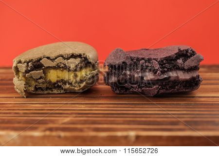 Set Of Bitten Macarons In Different Colors In Red Pastel Isolated Background
