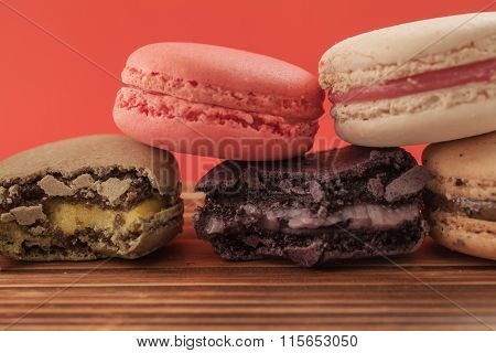 Set Of Macarons In Various Colors On Wood Table In Red Pastel Isolated Background. Some Of Them Are