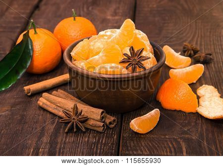 Tangerines with cinnamon stick and anisetree on old wooden table