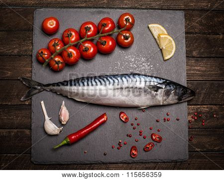 High Angle View Of Fresh Raw Whole Fish On Slate Cutting Board Surrounded By Fresh Herbs And Spices