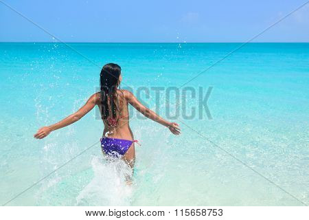 Beach vacation in tropical travel destination. Sexy woman in bikini feeling free swimming splashing water in blue ocean enjoying her sunny holidays. Concept of people having fun under the sun.