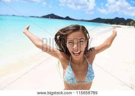 Exhilarated young woman screaming on beach. Portrait of cheerful female in bikini enjoying her summer vacation. Attractive tourist is standing with arms outstretched in nature.