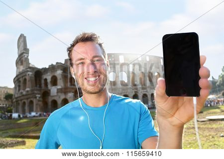 Smiling young runner showing smartphone with blank screen against Colosseum. Confident male jogger is listening music on sunny day. The empty space on mobile phone can be used for advertisement.