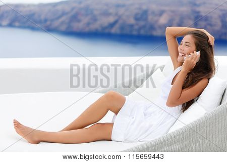 Happy young woman using smartphone while relaxing on couch. Smiling female talking on smart phone is at seaside resort terrace. Female tourist is wearing white sundress.