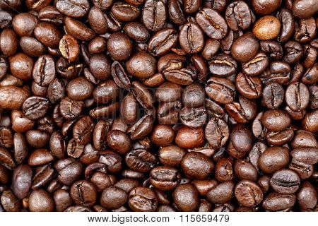 Coffee beans texture background. Closeup of fresh roasted bag of dark roast coffee beans pattern, useful for text copy space, element detail or advertisement background.
