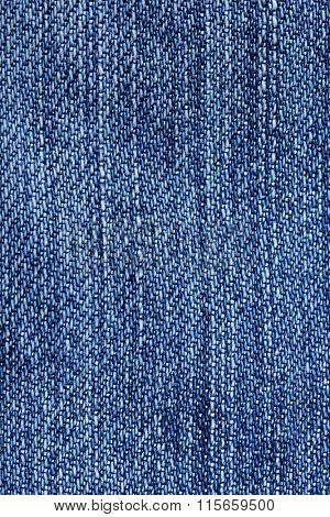 Jeans fabric background. Worn jean pants closeup of faded blue denim weave texture with vertical weave lines useful for elements of illustration, text copyspace or backgrounds.