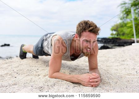 Crossfit training fitness man doing plank core exercise working out his midsection muscles. Fit athlete fitness cross training planking exercising outside in sand on beach.