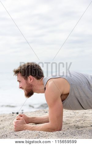 Core body workout fitness man doing plank exercises. working out his midsection muscles. Fit athlete fitness cross training planking exercising outside in summer on beach sand.