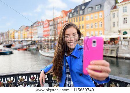 Asian tourist woman taking selfie at Copenhagen Nyhavn. Famous landmark, northern Europe destination, the old town waterfront water canal in the capital Kobenhavn in Denmark, Scandinavia.