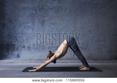 Young man practicing yoga in a urban background