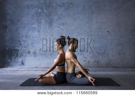 Young couple meditating together, sitting back to back
