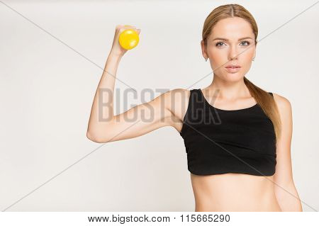 Sporty Girl Doing Exercise With Dumbbells And Looking At Camera