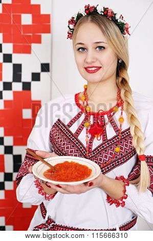 woman in national costume holding a plate of caviar