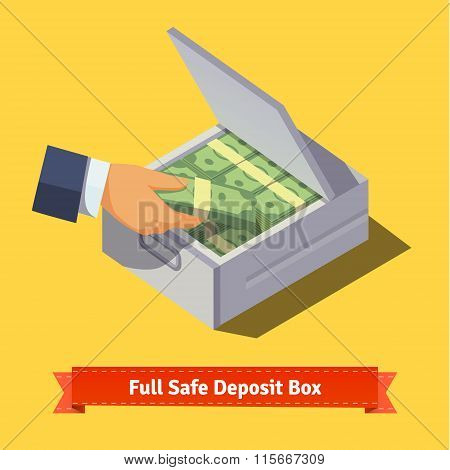 Hands putting cash stack to a safe deposit box