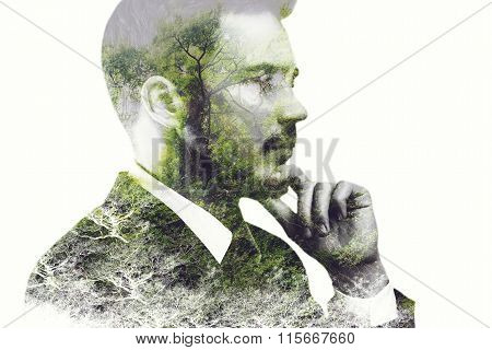 Think green. Digitally composed side view picture of young businessman holding hand on chin and looking away over the picture of green forest