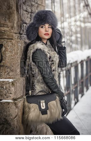 Attractive woman with black fur cap and gray waistcoat enjoying the winter. Side view of woman