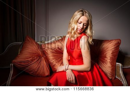 Portrait of pretty woman sitting in red dress