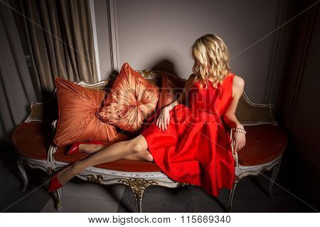 Sexy woman in red dress laying on fancy sofa