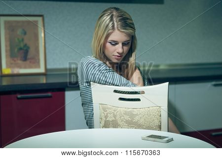 Young woman waits by the phone on a night kitchen