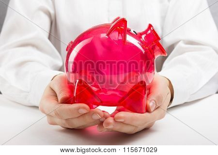 Savings concept. Woman holding piggy coin bank in hands