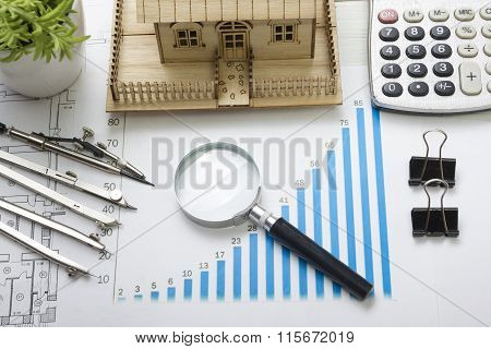 Model house, construction plan for house building, magnifying glass, divider compass. calculator. Re
