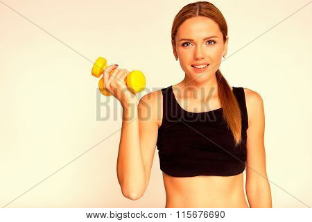 A Woman Holding A Yellow Dumbbell. Engaged In Fitness.