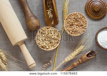 Wheat, Oat Grain Flour In A Wooden Basket. Wooden Spoon, Rolling Pin; Wheat Spikelets On The Table