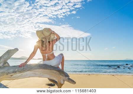 Portrait of young woman with straw hat sitting  on the beach