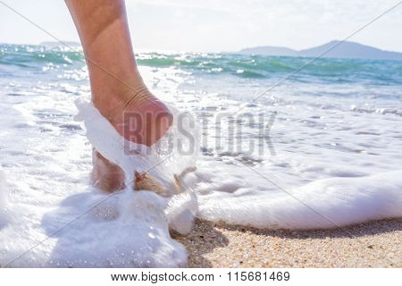 Woman foot on the beach walking in the water