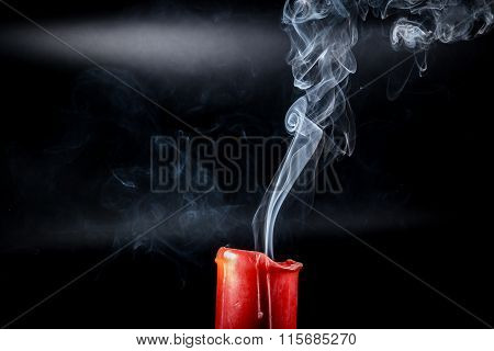 gray smoke flying upside from the extinct red candles