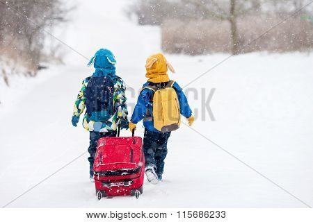 Two Little Children, Boy Brothers With Backpacks And A Big Red Suitcase