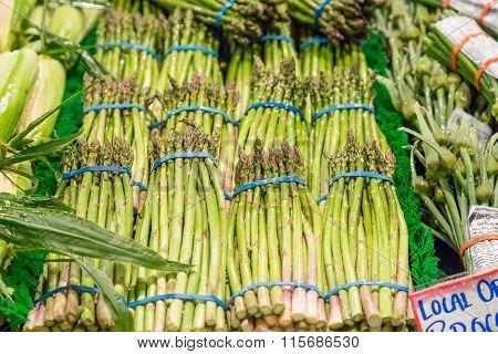Fresh Asparagus Bundles On Vegetable Stand