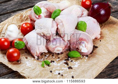 Raw Chicken Drumsticks with basil and pepper, salt, vegetables