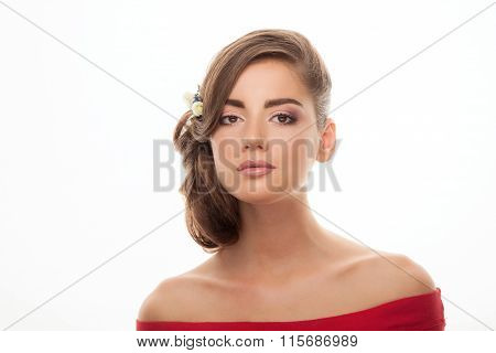 Closeup studio portrait of young elegant brunette woman with adorable makeup low bun hairstyle flowe