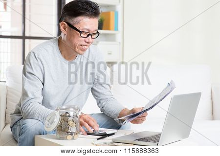 Portrait of 50s mature Asian man looking at bill and laptop in the living room. Saving, retirement, retirees financial planning concept.