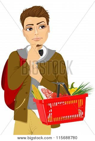 Thoughtful young man holding shopping basket full of food