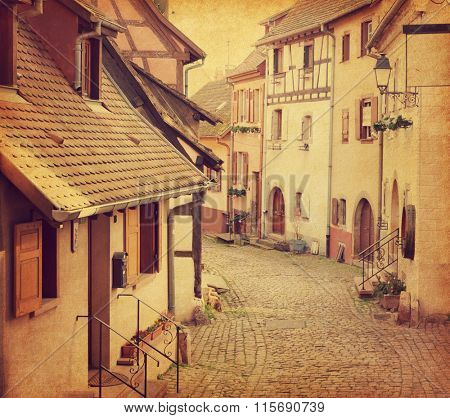 Winding street in Eguisheim, north-eastern France.  Photo in retro style. Added paper texture. Toned image
