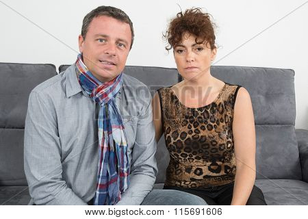 Happy Couple Middle Aged Sitting On Sofa At Home
