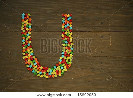 Letter U from alphabet made with star shape candy on a wooden background