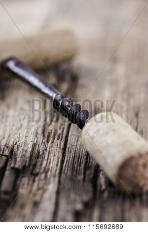 vintage corkscrew and wine cork on wooden surface macro closeup
