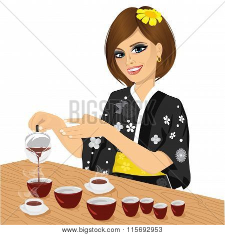attractive woman in black kimono pouring tea