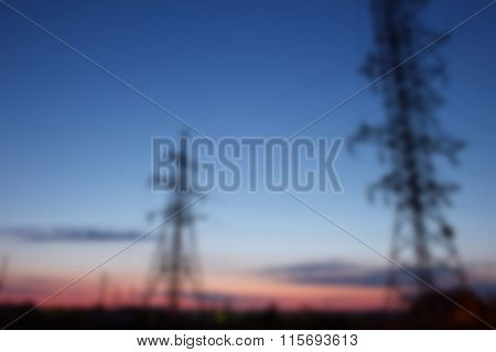 Blur Background Silhouette Of Electricity Transmission Pylon On Blue Sky