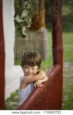 boy happy on the porch of an old house