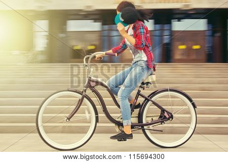 Girl Rides Bicycle At Sunset In The City
